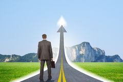 Person standing on roadway going up as arrow Stock Photography