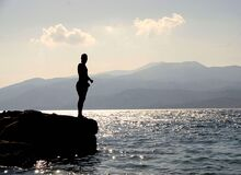 Person Standing on Rock Besides Sea Near Island during Daytime Stock Photography