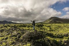 Person standing on rock with raised hands and looking at scenic. Icelandic landscape stock images