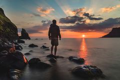Person Standing on Rock during Sunset Stock Image