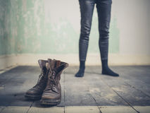 Person standing in room with boots. A young person is standing in an empty room with a pair of boots in the foreground Royalty Free Stock Image