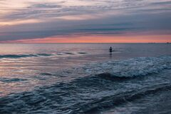 Person Standing in the Sea during Sunset Stock Photography