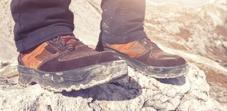 A person standing on the top of a mountain rock closeup hiking shoes. A woman standing on the top of a mountain rock with dirty hiking boots closeup Royalty Free Stock Photography