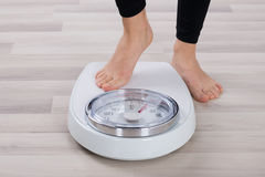 Person Standing On Weighing Scale. Low Section Of Person Standing On Weighing Scale royalty free stock image
