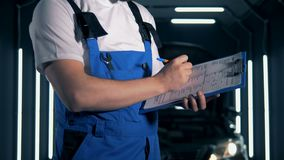 Mechanic writing on a paper on a clipboard, close up. stock video footage