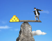 Person stands on rocky seesaw vs stack of gold. With sky background Royalty Free Stock Image