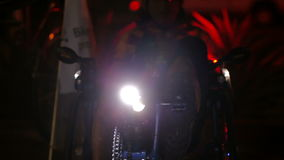 Person Starts Pedaling Recumbent Tricycle While Lights Flash. Red and blue lights flash as a person is sitting on a three wheeled bike. Person begins to pedal stock video footage