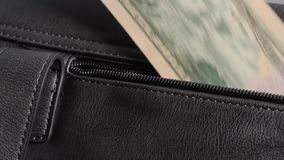 Person stiehlt eine Rechnung, Banknote von einer Frau ` s Handtasche Frauenhand nimmt fünfzig Dollar aus ihrer Taschentasche hera stock footage