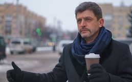 Mature man in a coat and scarf holding coffee trying to take a taxi royalty free stock photography
