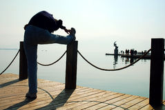 Person stretching on pier Stock Photo