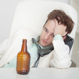 Person suffers from hangover sitting at a table Stock Photos