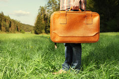 Person with suitcase on field. Side view of person with brown leather suitcase stood on grass field in countryside Stock Photography