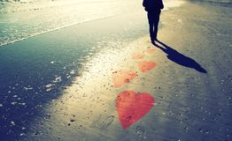 Person on sunny sandy beach with hearts background. Male person walks alone on sunny sandy beach with illustrated blurry pink red colored hearts Royalty Free Stock Images