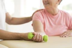 Person supporting exercising senior woman stock photos