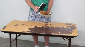 Person Sweeping Off en borttagen Tabletopklistermärke arkivfilmer