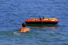 Person swimming around boat Stock Image