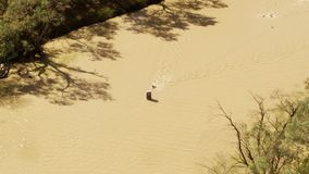 A person swimming on a brown river with trees. A birds eye view shot of people swimming on a brown river with trees in slow motion. Camera slowly moves to the stock footage