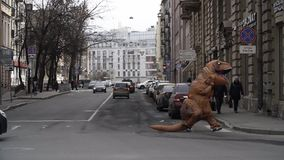Person in t rex costume prankster running at city street crosswalk. With lots of parked cars. Sunny day. Slow motion stock video