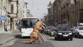 Person in T Rex costume prankster walking at city street crosswalk. With lots of parked cars. Sunny day. Slow motion stock video footage