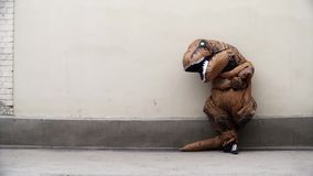 Person in t rex mascot costume leans on white wall and runs off. Person in t rex mascot costume cross arms leans on white wall and runs off at street on sunny stock footage
