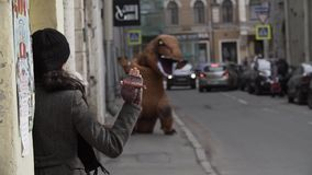 Person in t rex mascot costume waves arm at woman at city street alley. Cold sunny spring or autumn day, lots of parked cars. Slow motion stock footage