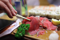 Person takes gyuniku tataki Royalty Free Stock Photo