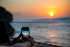 Person takes picture of sunset with their smartphone Royalty Free Stock Photography