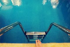 Legs with at the blue Swimming pool. A person takes a step towards the water in the home swimming pool. legs with at the blue Swimming pool Stock Photography