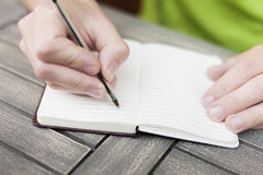 Person taking notes. Young man writing notes on a notebook with a pen, close-up view of hands Stock Image