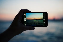 Person taking a photo of amazing sunset using smart phone camera Stock Images