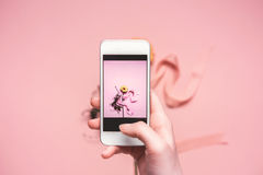 Person taking photo of flower with ribbon on smartphone. springtime concept Stock Photo