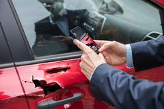 Person Taking Picture Of Damaged bil arkivbild