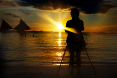 Person taking picture at sunset. Silhouette of person taking picture at sunset Royalty Free Stock Image