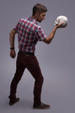 The person is tensely and emotionally standing full-length, with a skull in his hand Royalty Free Stock Images