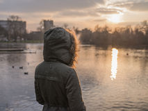 Person in thick warm coat by pond in winter Royalty Free Stock Photography