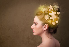 Person thinking with glowing puzzle mind. Young person thinking with glowing puzzle mind on grungy background Royalty Free Stock Image