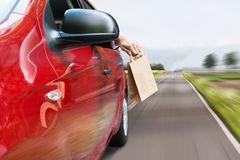 Person throwing trash out of car window. Close-up Of A Person's Hand Throwing Trash Out Of Car Window Stock Image