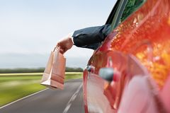 Person throwing trash out of car window. Close-up Of A Person's Hand Throwing Trash Out Of Car Window Royalty Free Stock Photos