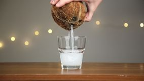Man throws ice into a glass, then pours coconut water. Against the background of the lights stock footage