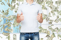 A person with thumbs up. Dollar notes are falling down from the ceiling. Stock Image