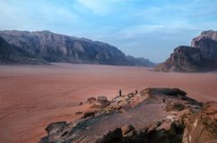 Person on a top of mountains in a desert. Sunset view. Nature. Tourist people enjoy a moment in a nature. Wadi rum national park -. Person on a top of mountains stock photos