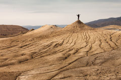 Person on top of mud and dirty volcanoes Royalty Free Stock Photos