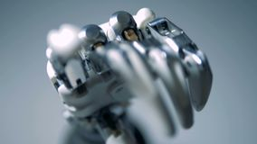 Person touches robotic hand, close up.
