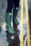 Person touching water pond in rubber boots Royalty Free Stock Photo