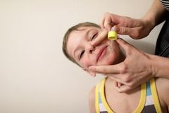 Person treats boy runny nose Royalty Free Stock Image