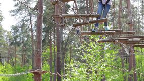 Person in treetop adventure park. Ropes between trees. Adventures and danger stock footage