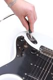 Person tuning a guitar from Stock Image