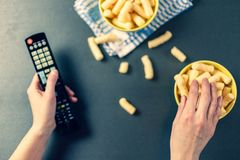 Person with TV remote watching tv and eating chips stock images