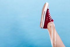 Person tying red sneaker with foot up Stock Photos