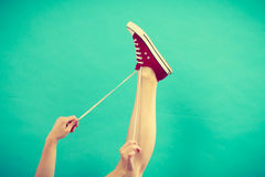 Person tying red sneaker with foot up Royalty Free Stock Images